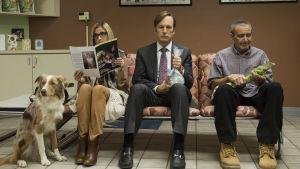 Juristen Jimmy McGill (Bob Odenkirk) sitter i en veterinärs väntrum med en vattenfylld plastpåse med en guldfisk simnmande inuti.