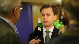 En man i kostym och grön slips intervjuas för TV.