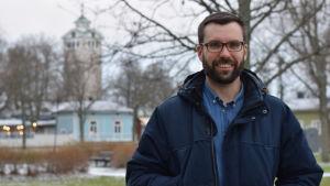 En mörkhårig man med skägg o glasögon står i en park. Kyrka i bakgrunden. (Ekenäs)