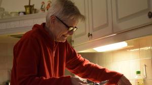 En äldre kvinna med röd fleecetröja och glasögon. Hon är i sitt kök..