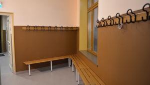 Väggarna i omklädningsrummet är bruna nertill och ljusa upptill, med svarta klädkrokar på väggen.