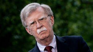 En man med grått hår, grå mustasch och glasögon, John Bolton, tittar åt sidan och ser allvarlig ut.