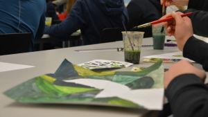 Ett papper ligger på bordet fyllt med flera olika gröna nyanser.