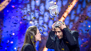 Vuoden 2018 Euroviisujen voittaja, Portugalin Salvador Sobral, nostaa lavalla päänsä päälle viisu-pokaalin, taustalla sataa konfettia. Vieressä myös toinen portugalilainen.