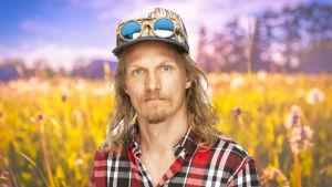 Kasper Ramström ser rakt in i kameran med en sommaräng som syns i bakgrunden.