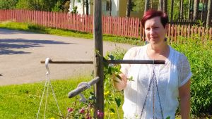 Anna står i blomstrande trädgård i starkt solljus med väg och staket i bakgrunden.