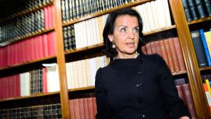 Anne Ramberg klädd i svart vid en bokhylla.