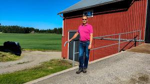En man står framför en åker och en röd träbyggnad.