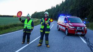 Två män i neonvästar och stoppskyldar i händerna står på en väg  och har en röd paketbil bakom sig. Kungsvägen stängdes av efter olyckan.