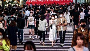 Människor i ansiktsskydd går över gatan i Tokyo.