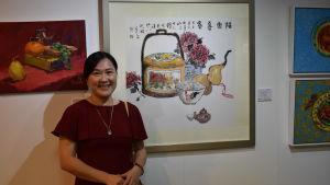 En leende kvinna med mörkt hår i en röd klänning och ett silversmycke runt halsen och ett armband av träpärlor står fram framför tavlor med motiv av mat och tittar in i kameran.