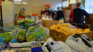 Människor som plockar livsmedel i kassar.
