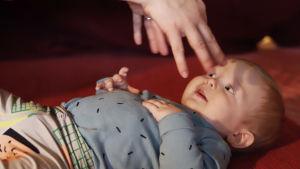 Soiva syli: vauva makoilee lattialla