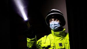 En brandmästare i gul jacka, vit hjälm och munskydd lyser med sin ficklampa i ett sotigt utbränt rum.
