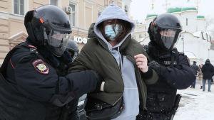 En person blir gripen av polis i samband med demonstration i Moskva.