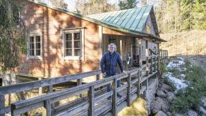 En man står på uteveranda, en slags bro vid en gammal byggnad.
