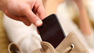 Hand plockar mobiltelefon ur väska.