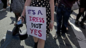 "Kvinna med skylten ""It's a dress, not a yes""."