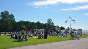 Människor sitter och har picknick på en gräsmatta.