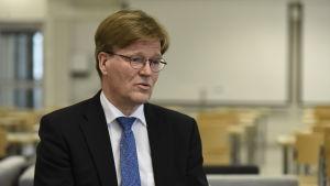 Tapio Kosunen har mörk kostym, runda glasögon och en blå slips.