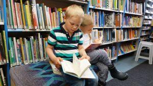 Mio och Ronja Eklund bekantar sig med de svenskspråkiga barnböckerna.