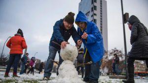 Människor bygger en snögubbe i Santiago 15.7.2017