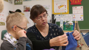Lärare hjälper elev att sy.