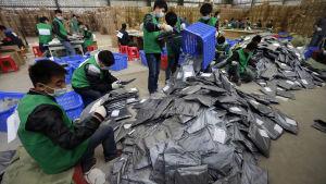 Kinesiska anställda vid logistikcentral sorterar nätförsändelser.