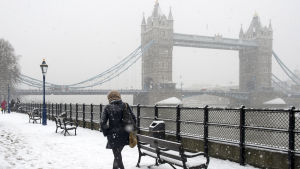 En kvinna går på en snöig väg med Tower bridge i bakgrunden.