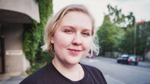 Aino Koivisto tittar rakt in i kameran. I bakgrunden en grönskande gatubild av Jyväskylä.