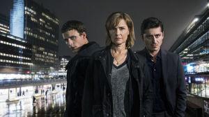 Seriens tre huvudpersoner iförgrunden med en nattmörk stad i bakgrunden.