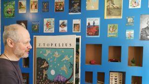 Bildkonstnären Alexander Reichstein intill den ännu ofärdiga blå ingången till utställningen Topelius sagoland i rådhusgallerian i Nykarleby. 2018.