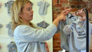 Blond kvinna i grå tröja hänger upp små tröjor för hundar på klädstång.