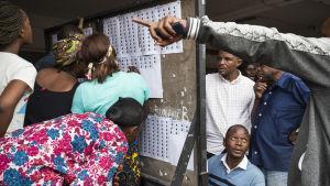 Väljare letar efter sina namn på valrullor i en vallokal i huvudstaden Kinshasa