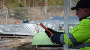 En man i gul reflexjacka och svart keps är beredd att skjuta iväg en nödraket. Han skyddar sig bakom en plexiglasskiva så att bara händerna och raketen kommer fram genom två hål i skivan.