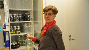 Retta Räisänen står och håller i en glasflaska.