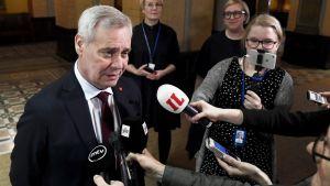 Antti Rinne pratar med pressen. I bilden syns också en handfull mikrofoner framsträckta mot honom.