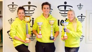 Två kvinnor och en man klädda i gula munkjackor håller upp fyra stora prispokaler.  Mot en vit vägg med svart tryck som  visar logon för dansföreningen Hurja Piruetti