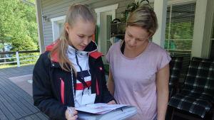Janni Heikkinen och Tanja Sirviö kollar på dokument gällande avloppsvattensystem.