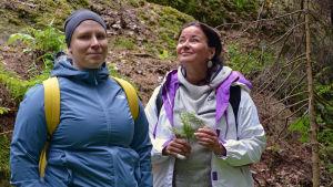 Två kvinnor står i skogen.