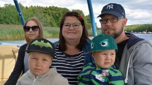 En familj med två vuxna å två barn sitter i ett kryssningsfartyg.