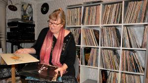 Ann_sophie sitter i en fåtölj och bläddrar bland vinyler.