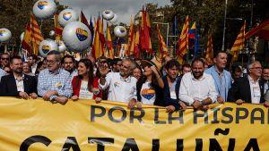 Espanjan yhtenäisyyden puolesta marssivat mielenosoittajat kuljettavat suurta banneria. Taustalla liehuu lippuja ja ihmiset kuljettavat kosolti ilmapalloja.