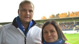 Två fotbollssupportrar, Johan och Lotta Liljeström, han med vit jacka och blå halsduk, hon med röd jacka och blå halsduk.