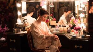 Judy Garland (Renée Zellweger) sitter i sin loge vid sitt skrivbord och ser ledsen ut.