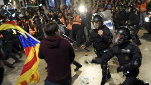 Poliser med batonger angriper en demonstrant som bär på Kataloniens flagga