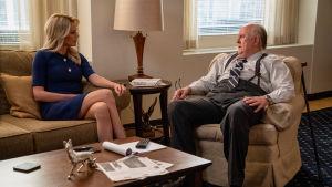 Roger Ailes (John Lithgow) i samspråk med Megyn Kelly (Charlize Theron) i soffan på ett kontor.