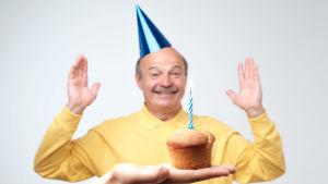 Äldre man i partyhatt ler, någon räcker fram en mufin med ett ljus till honom