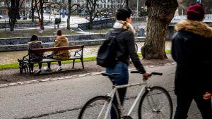 Vänner invid Aura å, ett par på en bänk och två kvinnor promenerar.
