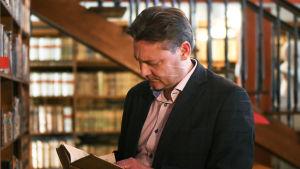 Stefan Hagman läser en bok i Borgå gymnasiums gamla bibliotek.
